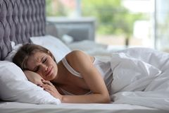 Depressed young woman in bed. At home Stock Photography