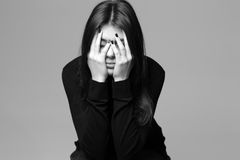 Depressed young woman with hands over her head