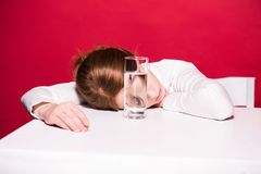 Young woman with glass of water. Depressed young woman leaning at table with glass of water isolated on red Stock Photos