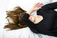 Depressed young woman is lying in her bed, covering her eyes. Royalty Free Stock Photos