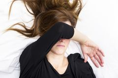 Depressed young woman is lying in her bed, covering her eyes. Stock Photography