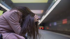 Depressed young woman suffering psychological problems sitting in subway station royalty free stock photography