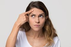 Depressed young woman touching forehead worried about skin wrinkle royalty free stock image