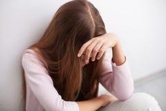 Depressie in adolescentie - de jonge zitting van het tienermeisje door muur stock foto