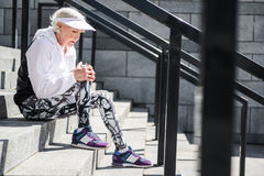 Depressing aged woman having rest on stone stadium ladder. Sad old lady is sitting on stairs and embracing one bent knee leg with pain. She is looking down. Copy stock photography