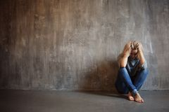 Depressing girl. Young beautiful blonde in a gray sweater and jeans stock photos