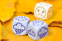 Depressing and sad weather of autumn shown on dice Royalty Free Stock Photo