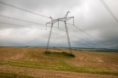 Power lines on the field in cloudy weather. Stock Images