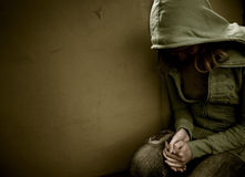 Depression. Teenage girl siting against wall in a depressed state Stock Image