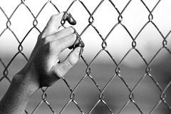 Depression. Close up of hand on chain-link fence. Limited depth of field, converted to black and white with added grain stock photo