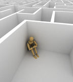 Depression. Depressed mannequin sitting in the corner of a big maze Royalty Free Stock Photo
