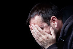 Depression. A depressed man with his hands over his face, shot on black Stock Photography