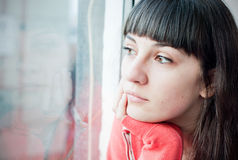 Depression. Depressed young woman looking through the window Stock Photos