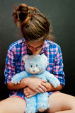 Depression. A depressed teen clutches a teddy bear for comfort royalty free stock image