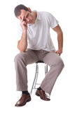 Depression. A young man, sitting on a stool, thinking. Isolated on white background Stock Image