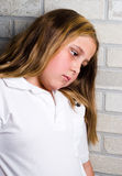 Depression. A young depressed girl is leaning her head against some bricks Royalty Free Stock Image