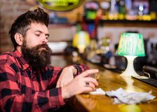 Depression and alcoholism concept. Man with sad face sit alone. In bar or pub near bar counter. Hipster holds glass with whiskey or alcoholic drink. Guy spend stock images