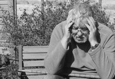 Depression-black and white. Depression in black and white. A senior man with his walking stick sitting on a bench with his head in his hands Stock Images