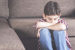 Depression concept with sad kid. Unhappy kid lost in his thoughts Stock Photography