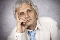 Depression. Elderly man lost in thought on silver background Royalty Free Stock Photo