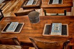 Teacher's Desk. Depression era student desks in an historic schoolhouse. Image shows McGuffy readers, student slate (personal chalkboard) and lunch pail on an stock photo