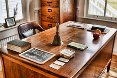 Teacher's Desk. Depression era teacher's desk in an historic schoolhouse. Image shows a student's  slate (personal chalkboard) book, recess bell, an apple, an Stock Images