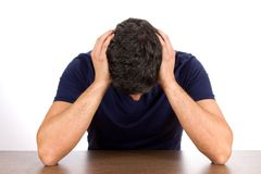 Depression And Failure. Downcast man holds his head as he suffers from depression and failure Stock Photos