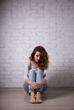 Depression and loneliness - sad young woman sitting on the floor Stock Photography
