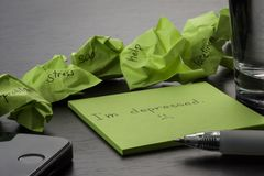 Depression. The phrase `I`m depressed` is written on a green sticky note on wooden black table. Crumpled sticky notes are scattere stock images