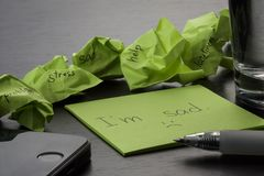 Depression. The phrase `I`m sad` is written on a green sticky note on wooden black table. Crumpled green sticky notes are scattere stock image