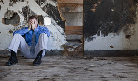 Depression and Sadness. Man in a shirt and tie acts depressed inside a run down home royalty free stock photography