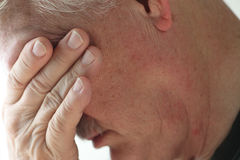 Depression in senior man. Depressed older man averts his head, covering his eyes with a hand Royalty Free Stock Photography