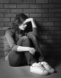 Depression and Sorrow. Teenage girl siiting against brick wall in a depressed state Royalty Free Stock Photography