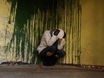 Depression and sorrow. Teenage girl sitting against dirty wall Stock Image