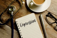 Depression. Top view of notebook written with DEPRESSION with stethoscope pen,sunglasses, and a cup of coffee on wooden background. Medical and healthcare theme Royalty Free Stock Photos
