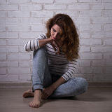 Depression - unhappy woman sitting on the floor Stock Images