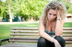 Depression - worried young woman. Sitting on bench outdoor in park Stock Photo