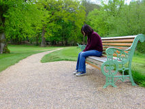 Depression - young female. A young female sitting on a park bench, looking depressed and alone Stock Photo