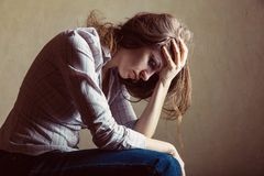Depression. Young sad girl sitting alone in an empty room Stock Photography