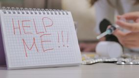 Desperate child in depression. suicide. Depressive child sitting on the floor with a syringe. Close up hands. In the foreground is a sign saying help me, pills stock footage