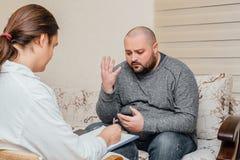 Depressive fat man talking with psychologist. Psychologist writes notes. Depressive fat men talking with psychologist. Psychologist writes notes Royalty Free Stock Image