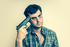 Depressive man trying to commit suicide with a gun. Aiming on his head - retro style Stock Image