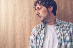 Depressive sad man profile portrait. Male person with unhappy gloomy facial expression leaning on to wall and looking to a side Royalty Free Stock Photos