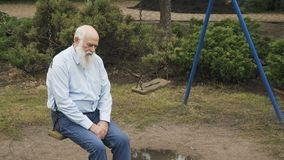 Depressive senior man on the swing. Sad senior man recollects childhood and swings on teeterboard. Depressive gray-haired man spend his leisure time outdoors stock footage