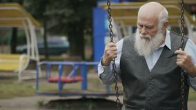 Depressive senior man swings on seesaw in slowmotion stock video