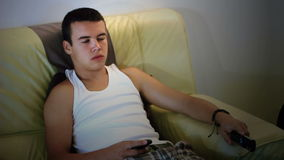 Depressive young attractive teenager boy  watching television on sofa stock footage