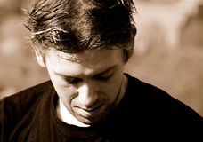 Depressive young man. Portrait of a depressive young man looking down (monochrome stock photo