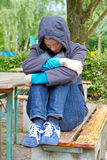 Depressive, young woman. Depressive woman sitting on a bench on laken Stock Photo