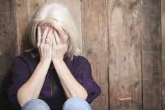 Deprima la persona senior con fondo di legno Fotografia Stock Libera da Diritti