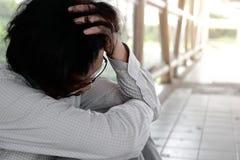 Deprimente ha sollecitato il giovane uomo asiatico che tocca la testa e che ritiene deludente o esaurito Concetto disoccupato del fotografie stock